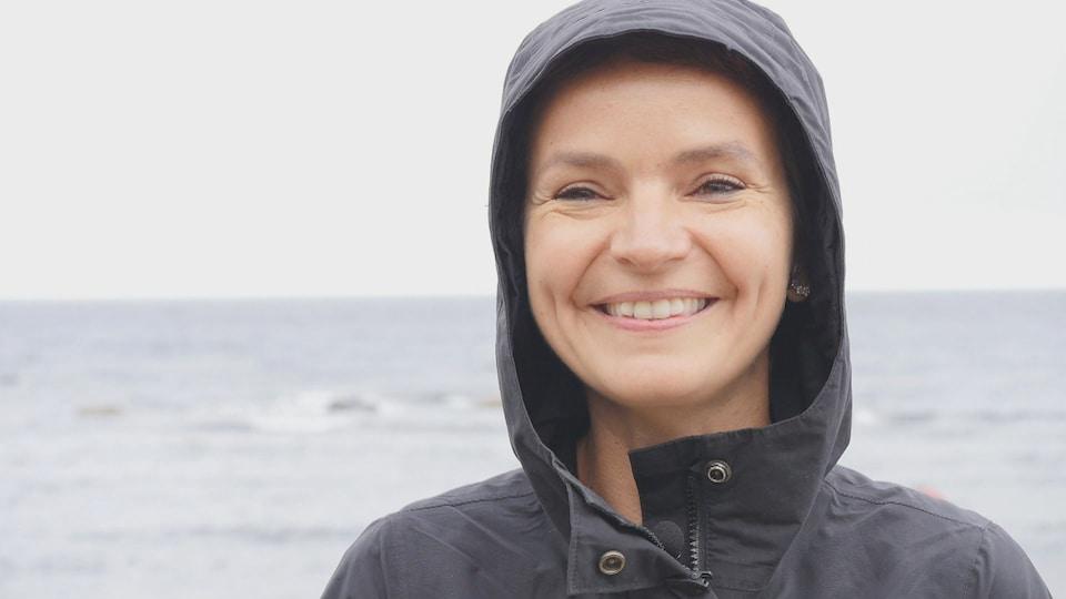 Portrait d'une femme portant un capuchon sur la tête.