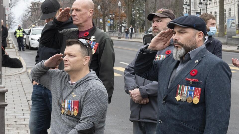 Des anciens combattants portant des médailles, dont l'un en fauteuil roulant, font le salut militaire.