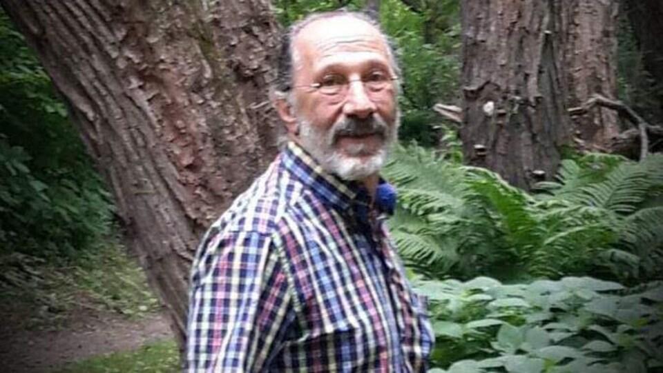 André Belisle pose dans une forêt.