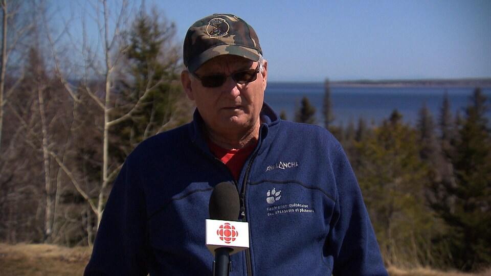 André Boulianne en entrevue sur une colline devant un lac au printemps.