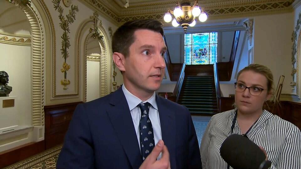 André Fortin répond aux questions des journalistes dans les couloirs de l'Assemblée nationale.