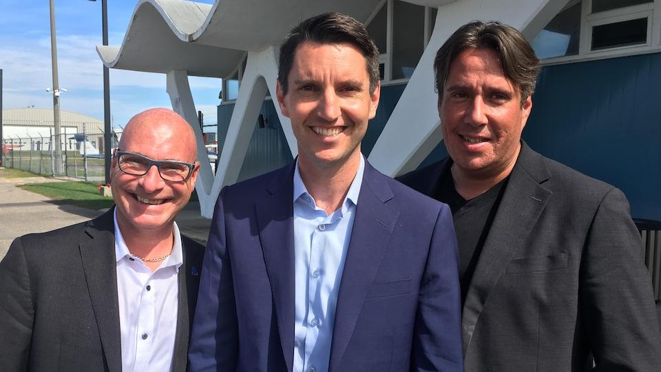 Les trois hommes sur le terrain de l'aéroport de Trois-Rivières