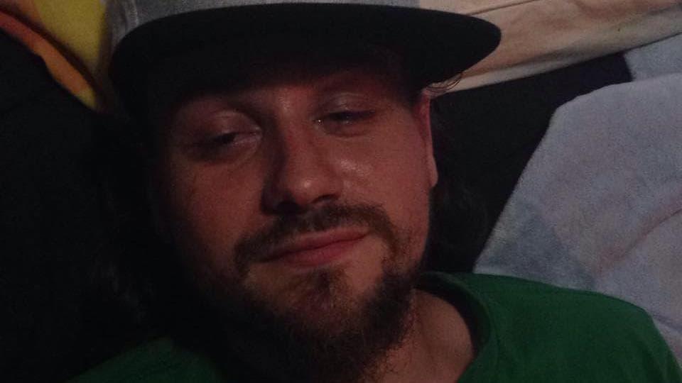 L'homme porte la barbe et la casquette, ainsi qu'un t-shirt aux couleurs des Celtics de Boston, une équipe de basketball.