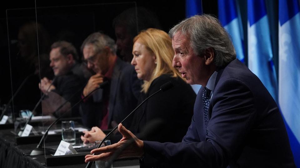 André Lamontagne assis à la table de presse en compagnie de trois invités.