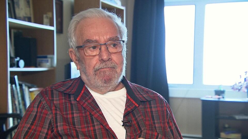 Une homme âgé en entrevue.