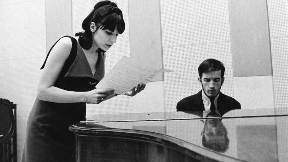 André Gagnon est assis au piano tandis que Renée Claude examine une partition.
