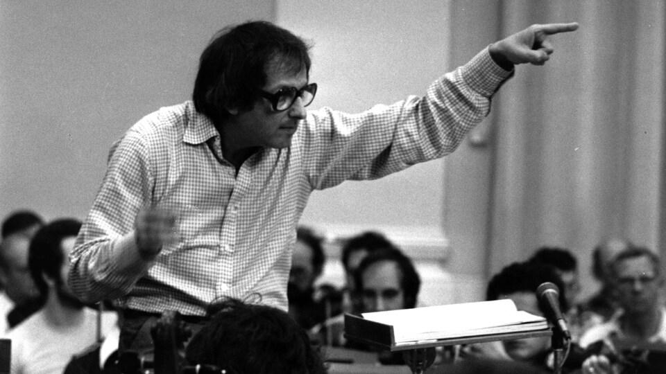 Le musicien André Previn, vêtu d'une chemise à carreaux, a la main gauche levée alors qu'il mène un orchestre au milieu d'une pièce.