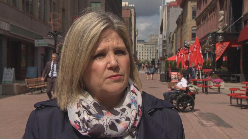 Andrea Horwath, chef du NPD Ontario porte un petit manteau bleu marine et un foulard à fleurs elle est dans une rue d'Ottawa.