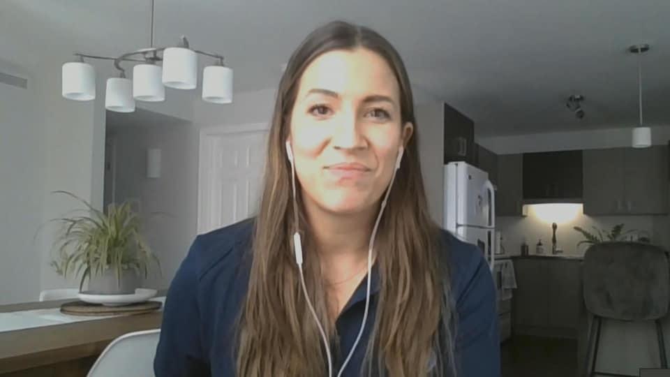 Une femme en visioconférence. Elle a des petits écouteurs dans les oreilles.
