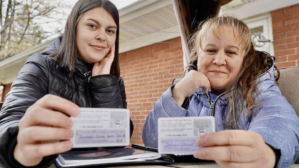 Deux femmes tenant leur carte d'assurance-maladie signée pour le don d'organe.