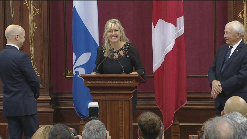 Andrée Laforest lors de son assermentation au Salon rouge de l'Assemblée nationale. Elle porte une robe noire et se tient derrière un lutrin placé entre un drapeau du Québec et un drapeau du Canada. La ministre affiche un large sourire.