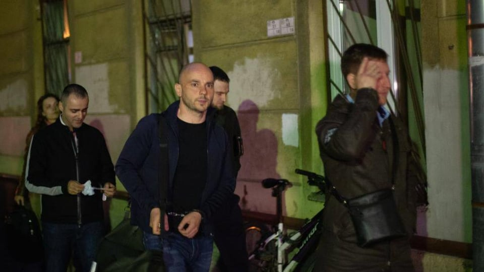 Andrei Pivovrov walks in and is taken away by police officers, handcuffed.