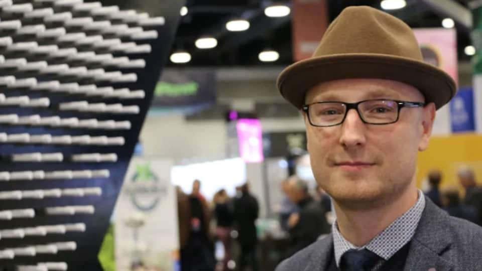 Gros plan sur le visage d'un homme portant des lunettes et un chapeau.