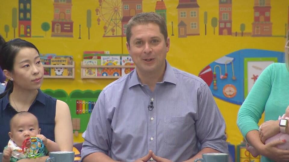 Un homme en chemise s'adresse à la presse assis entre deux femmes portant des enfants.