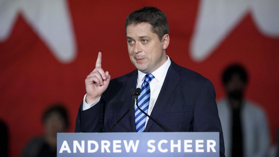 Le chef conservateur fédéral, Andrew Scheer, pointe un doigt en l'air pendant un discours, devant un pupitre.