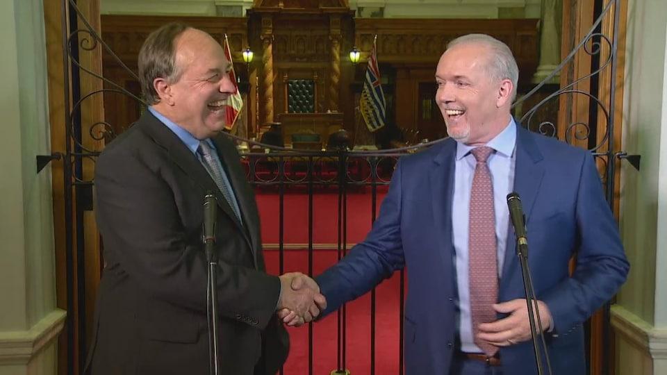 Deux hommes d'âge mûr en complet-cravate, se serrent la main et sourient.