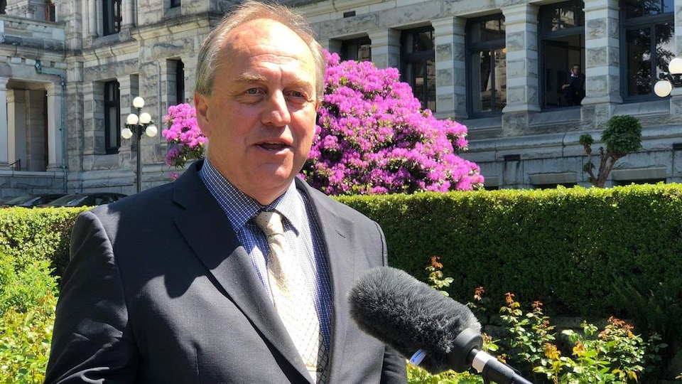 Andrew Weaver, derrière un microphone, en point de presse devant l'édifice de l'Assemblée législative de Victoria.