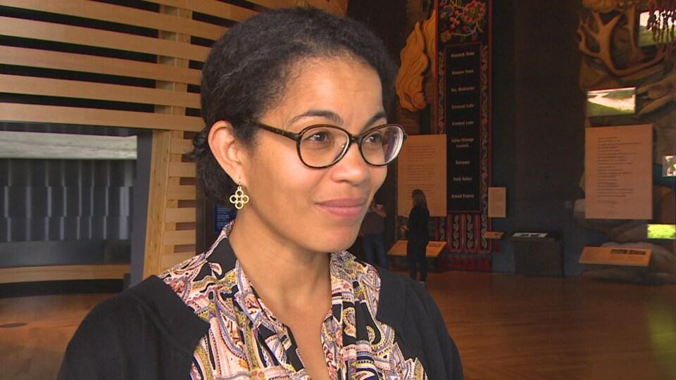 Une femme aux cheveux noirs attachés et à lunettes, dans une galerie d'un musée devant de grandes oeuvres autochtones.