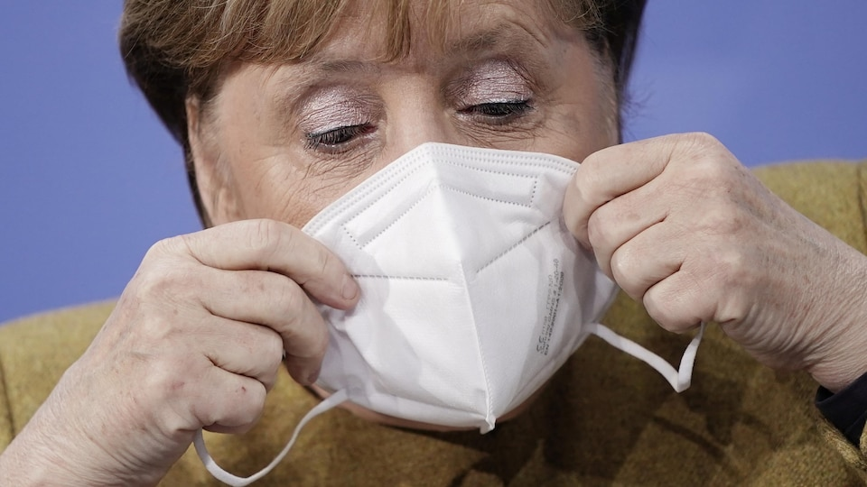 Mme Merkel mettant son masque.