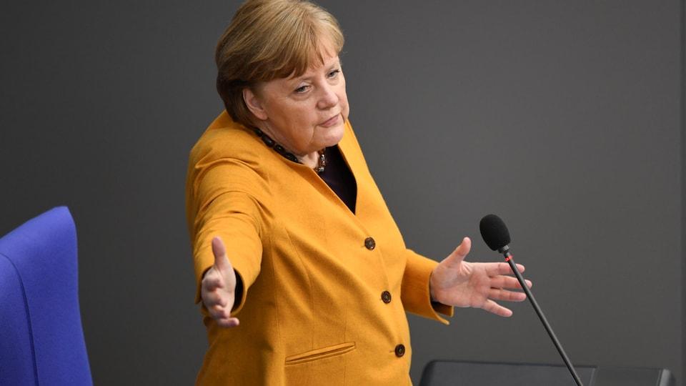 La chancelière, qui porte un tailleur jaune, écarte les mains.