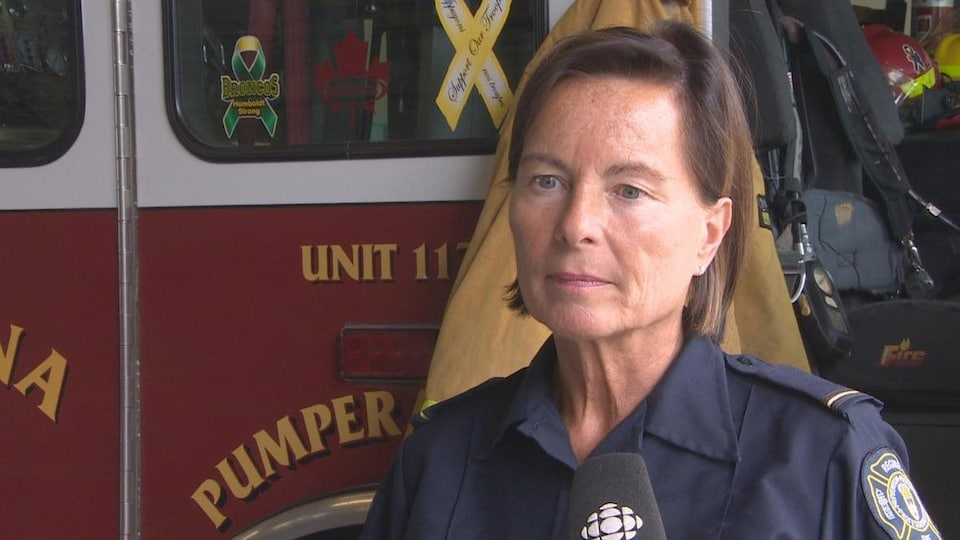Angela Prawzick devant un camion de pompier.