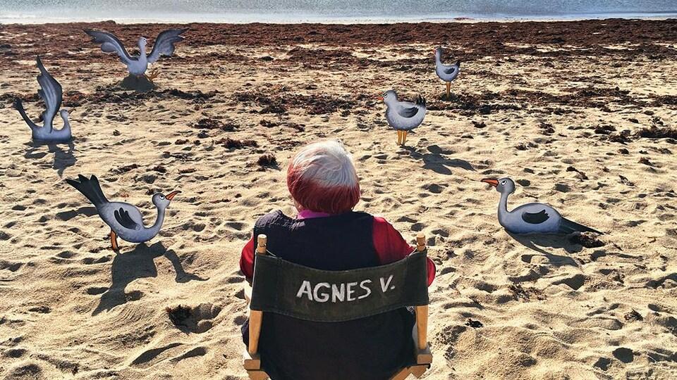 Une femme est assise sur une chaise, sur une plage. Il y a des oiseaux en carton autour d'elle.
