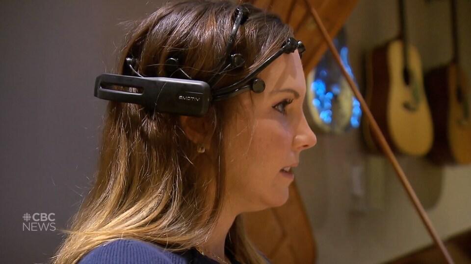 Une femme porte un casque de lecture des ondes cérébrales dans une pièce avec des instruments de musique.