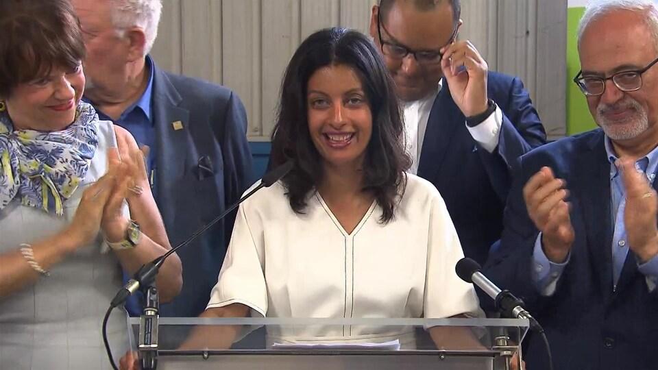 Une femme souriante, entourée de trois hommes et d'une femme qui l'applaudissent.