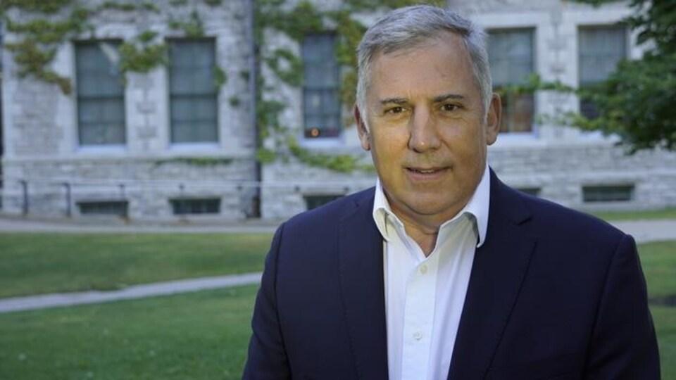 Un homme sourit à la caméra, devant un bâtiment d'Ottawa.