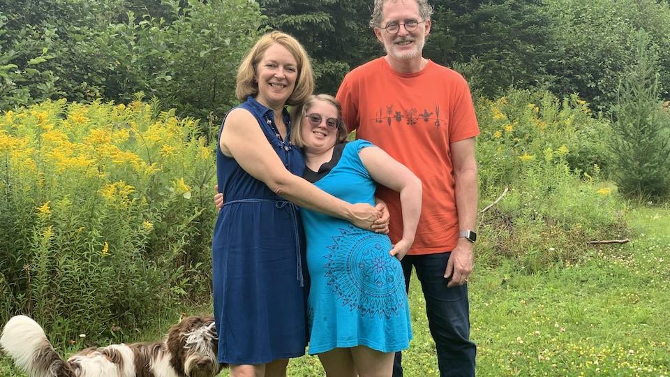 Debout devant des arbustes verts, une mère et un père entourent de leurs bras leur fille.