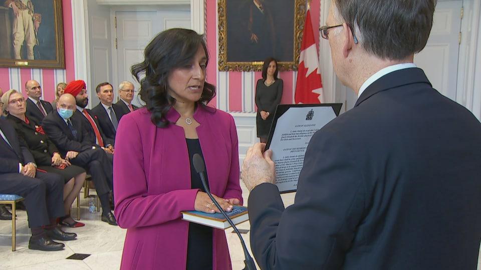 Anita Anand prête sermet en posant la main sur un livre dans salle bondée de Rideau Hall.