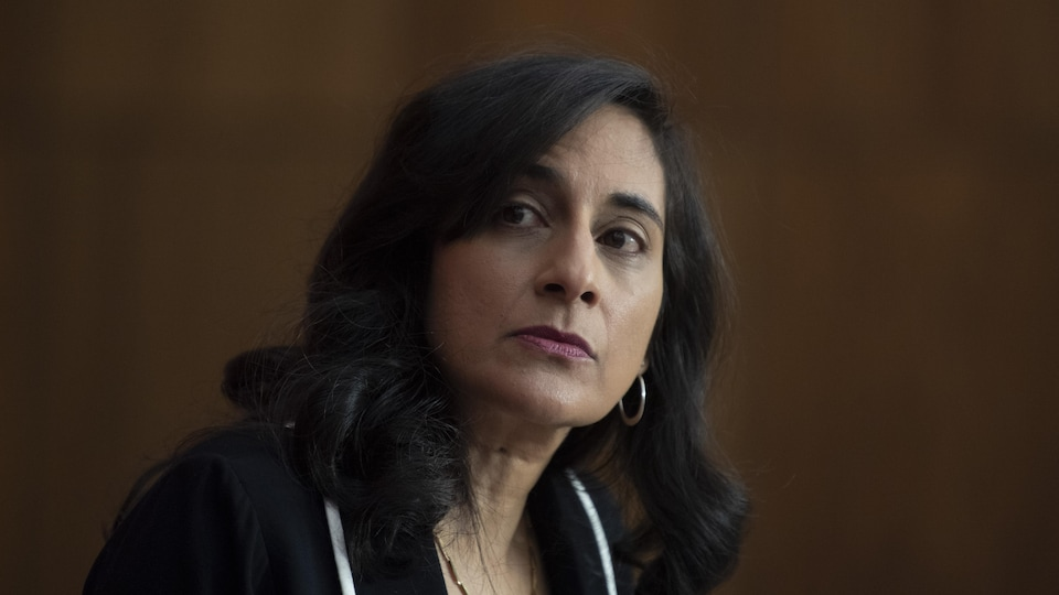 La ministre fédérale de l'Approvisionnement, Anita Anand, regarde à sa droite, l'air attentif.