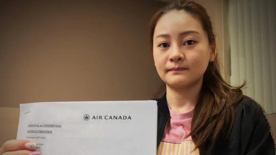 Une jeune femme montre à la caméra le document légal que lui a fait parvenir Air Canada.
