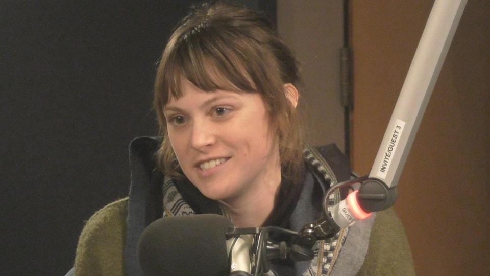 Anna-Laure Koop devant un micro dans un studio.