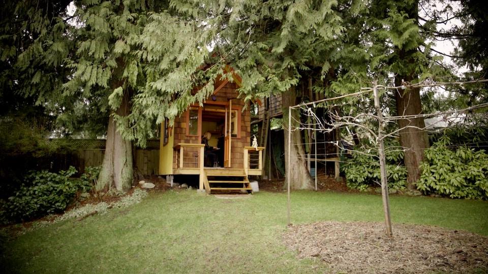 Sous des arbres conifères, une petite maison de bois dans laquelle on y voit la musicienne Anna Lumière assise à son piano.