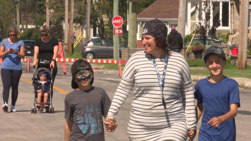 Annabelle Céré marche main dans la main avec deux jeunes garçons.