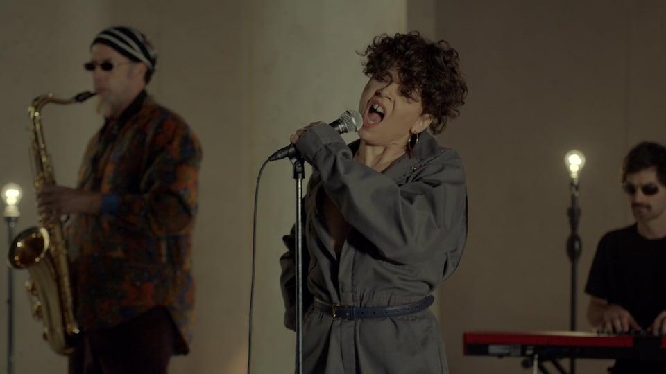 La femme chante avec des musiciens.