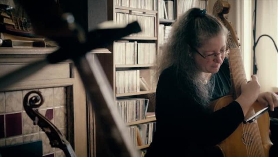 Une musicienne joue de la lyre de gambe