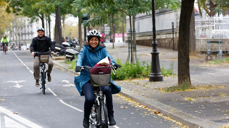 On voit Anne Hidalgo à vélo, de face.