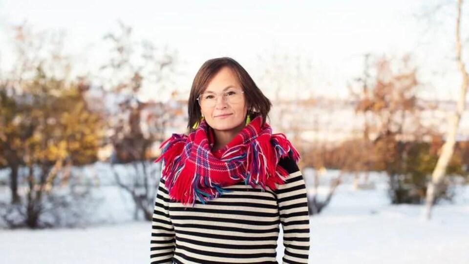 Une femme aux cheveux raides et foncés, et aux yeux bridés, pose au milieu d'un paysage enneigé.