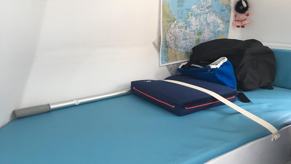 Une couchette de bateau avec une carte géographique du Grand Nord et une poupée Inuit accrochés au mur.