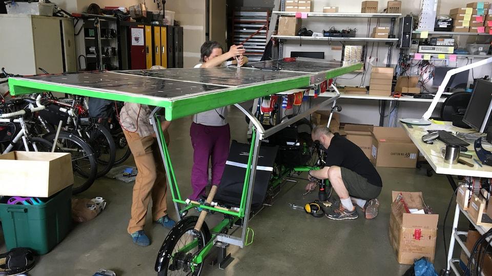 Trois personnes réparent un vélo avec un panneau à énergie solaire dans un atelier.