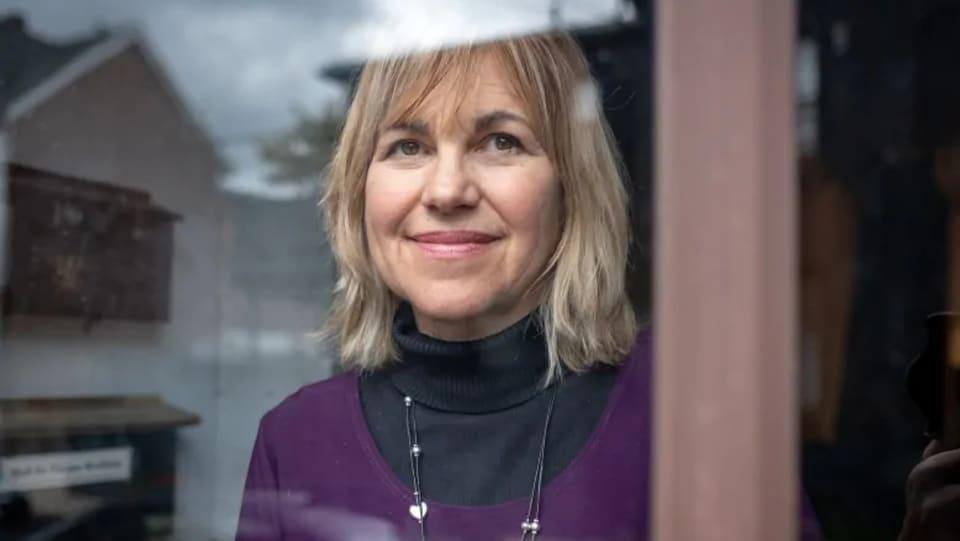 Anne Woolger regarde par la fenêtre en souriant.