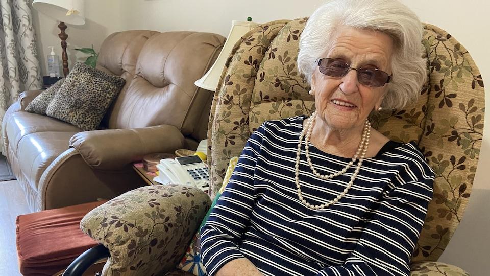 Une femme centenaire assise dans un fauteuil.
