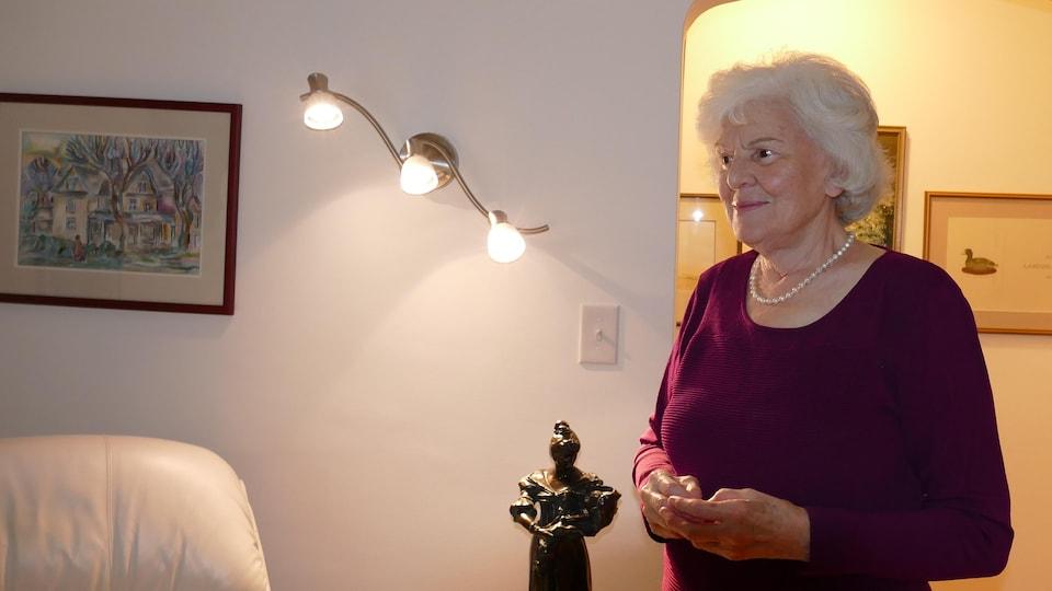 Annette, debout dans son salon.