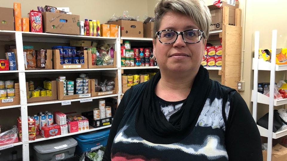 Une femme se tient debout devant des étagères contenant des denrées non périssables.