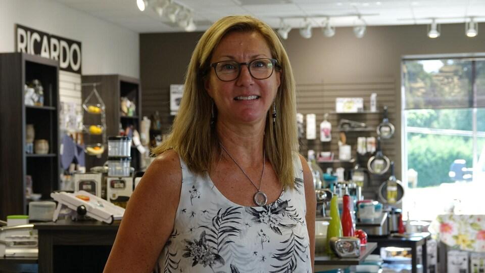 Annie Laviolette dans son magasin avec des articles de cuisine à l'arrière.