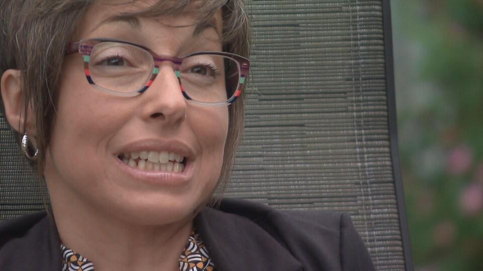 Une femme aux cheveux courts et portant des lunettes assise sur une chaise en entrevue à la caméra.