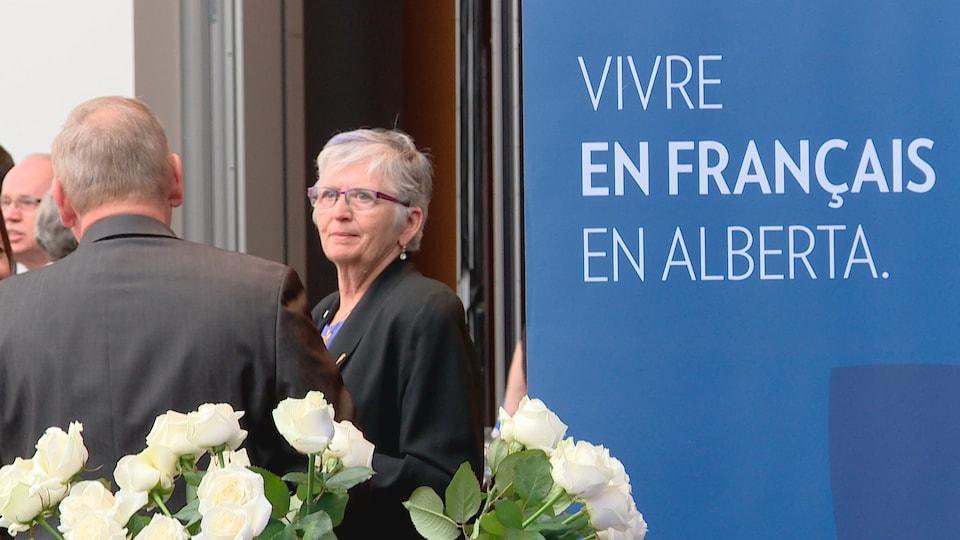 Une bannière où se lit «Vivre en français en Alberta», à droite, avec la députée Annie McKitrick qui écoute un interlocuteur, vu de dos, avec des roses blanches au bas de l'image.