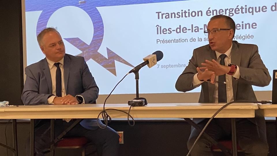 Jonatan Julien et Éric Fillion assis derrière une table avec un micro et une présentation numérique derrière eux.
